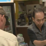 Customers of all races help Asian Donut shop owner.