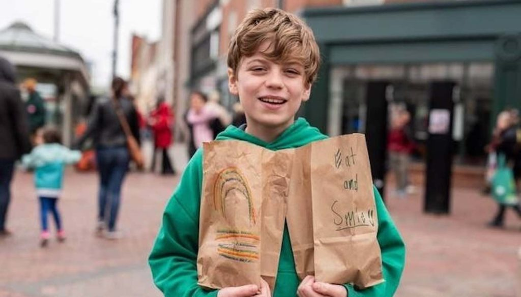 White kid gives food to homeless people.